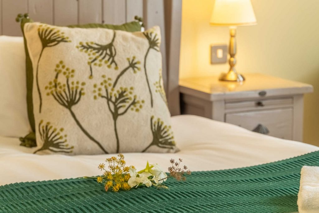 Freshly cut flowers and crisp bed linen in The Stables Room